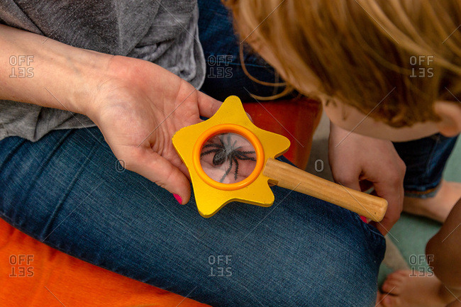 Toddler boy looking at fake spider under magnifying glass with his mother