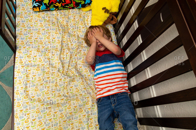 Toddler boy lying on his bed and covering his eyes
