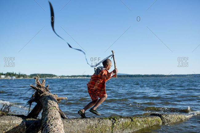Boy running with streamer on a stick at the coast