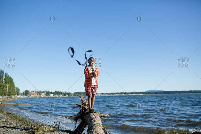 Boy standing on a log waving a streamer on a stick on a breezy day at the beach