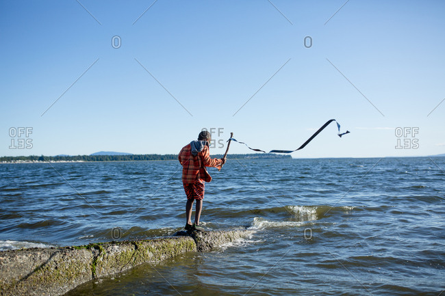 Boy holding streamer on a stick at the coast