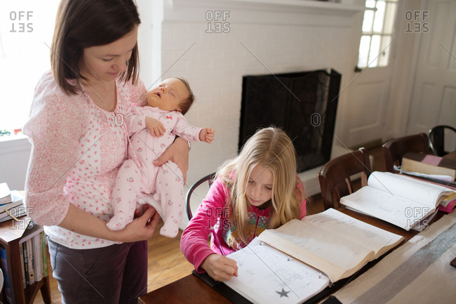 Young girl doing homework at dining room table as mom looks on holding sleeping baby