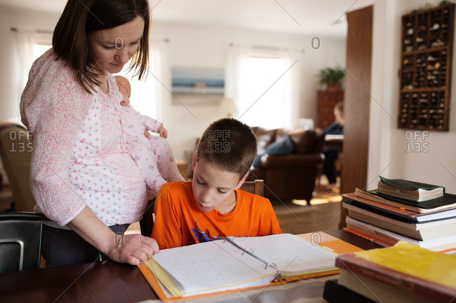 Mom carrying sleeping baby looking over son's homework at dining table