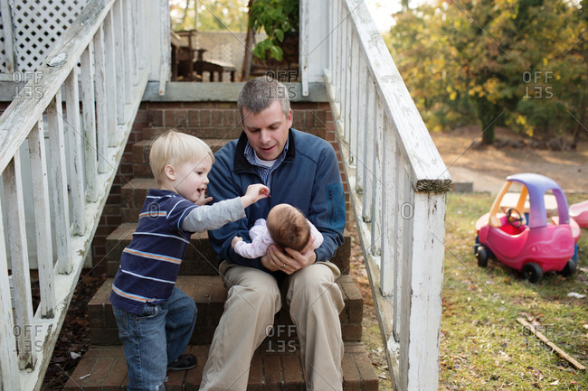 Dad sitting on back steps of house cradling newborn baby and brother plays