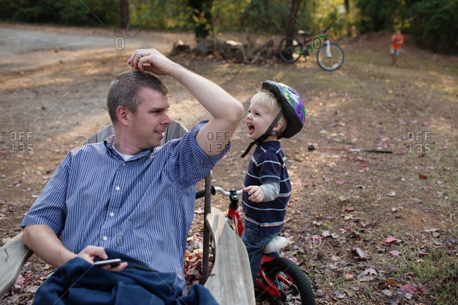 Little boy on bicycle laughing after dropping something on dad's head in backyard