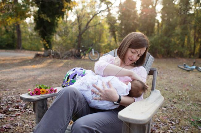 Mother breast feeding baby in backyard