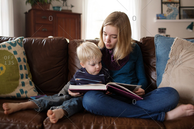 Young girl reading story to little brother on couch