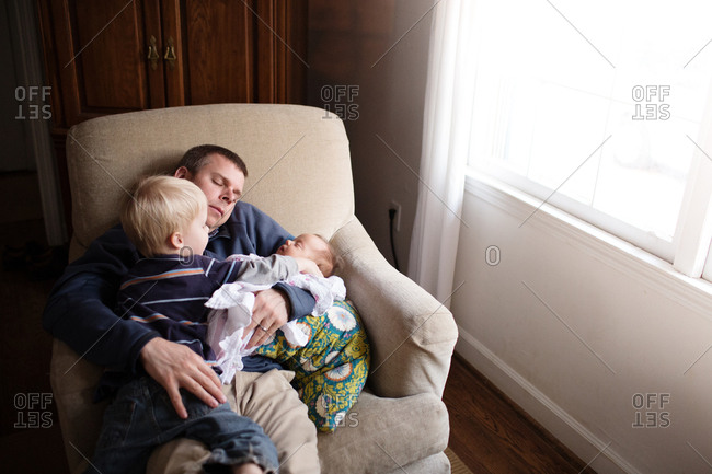 Dad napping with baby in his arms as little boy watches