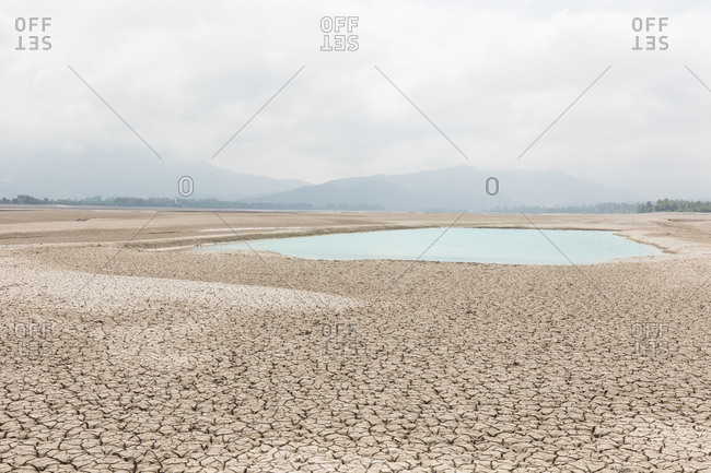 Small pool of water in otherwise arid lake bed of Forggensee in Germany
