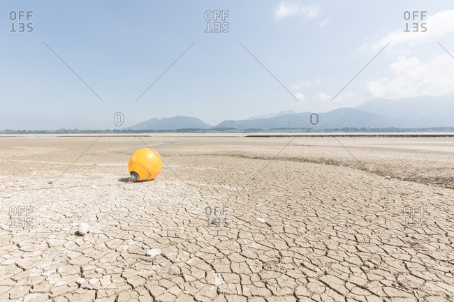 Mooring buoy sitting on cracked earth of lake bed of Forggensee in Germany