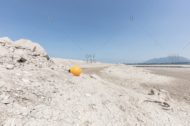 Yellow buoy lying next to tree stump on bed of arid dirt of lake Forggensee in Germany