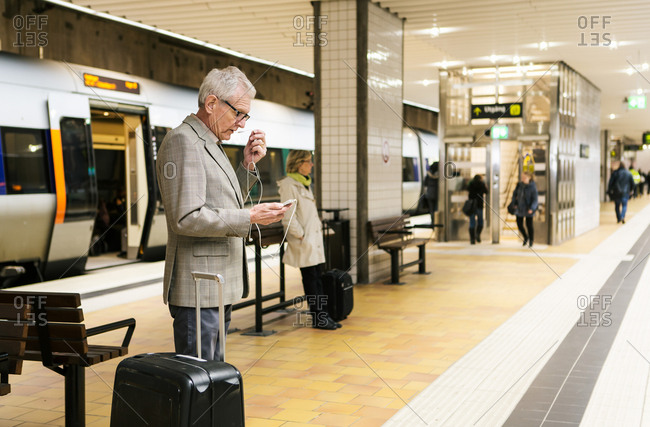 Senior male commuter using smart phone while standing by luggage at subway station