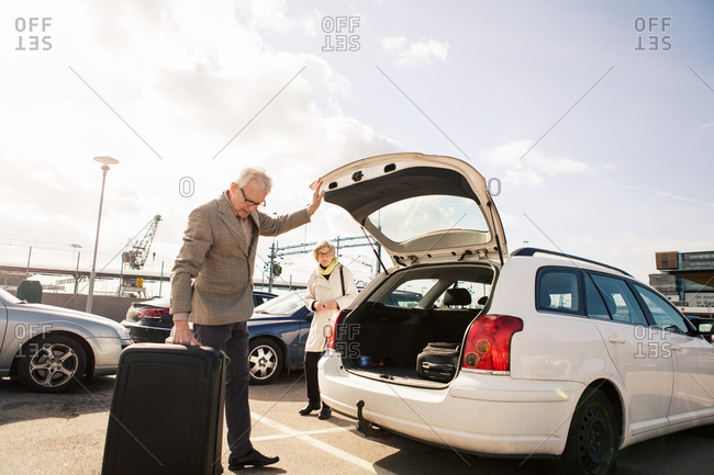Senior man loading luggage in car trunk with woman standing in parking lot against sky