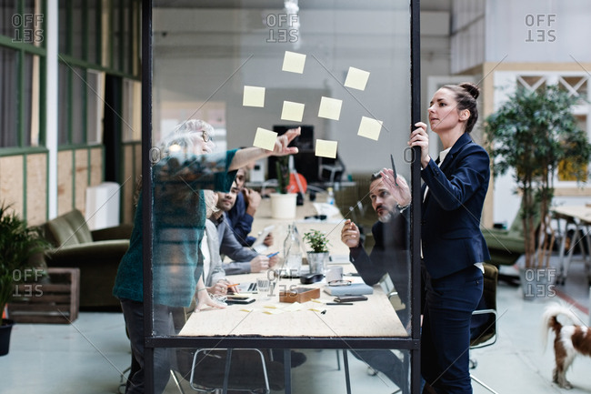 Businesswomen explaining adhesive notes to colleagues in meeting at office