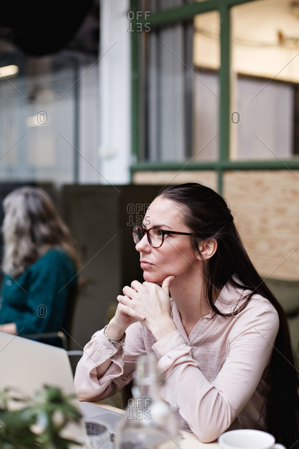 Thoughtful businesswoman sitting with hands clasped at table in creative office