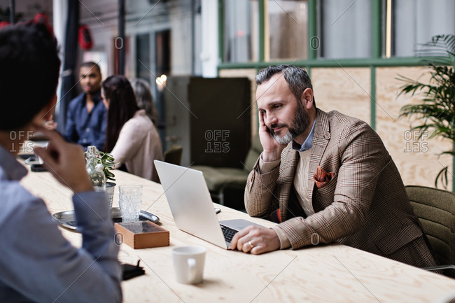 Tired businessman using laptop while sitting with colleagues at table in meeting