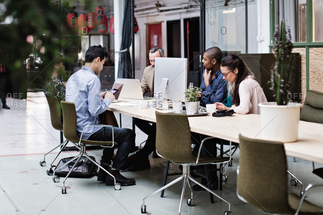 Business coworkers using technologies at table in office meeting
