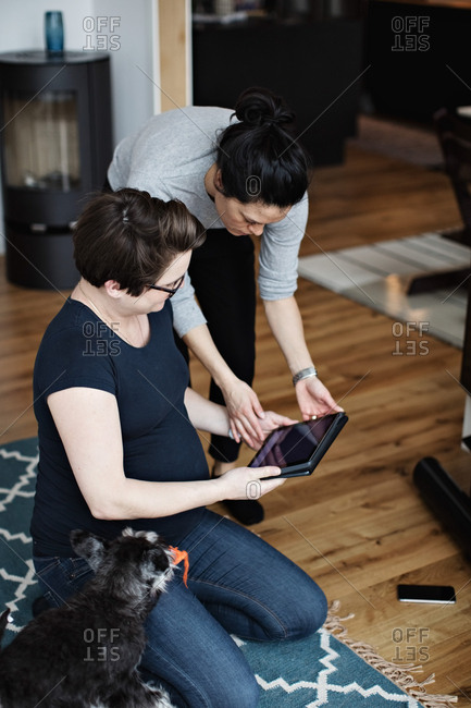 Woman showing digital tablet to girlfriend sitting by dog on carpet in living room