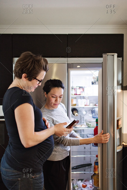 Woman showing mobile phone to girlfriend while standing by open refrigerator in kitchen