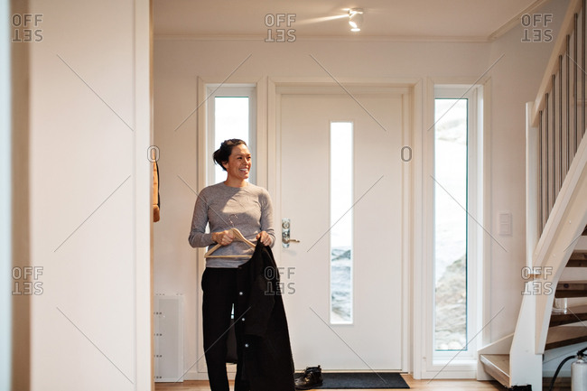 Smiling woman looking away while hanging coat to coat hanger against door at home