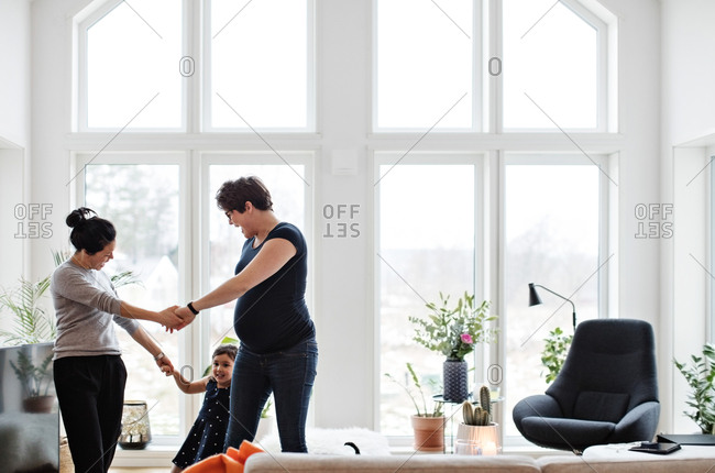 Mothers and daughter holding hands while playing in living room at home