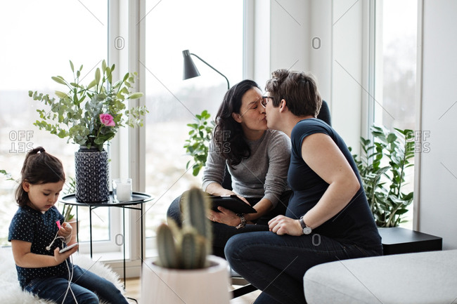 Lesbian couple kissing while girl using mobile phone in living room at home
