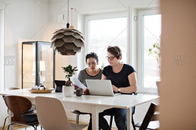 Lesbian couple discussing financial bills over laptop while sitting at table