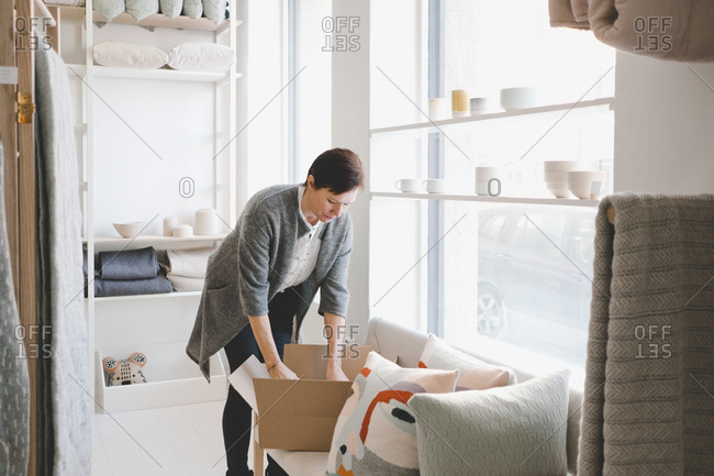 Mature female craftsperson unpacking products from cardboard box in store