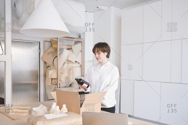 Young female craftsperson holding bottle in workshop