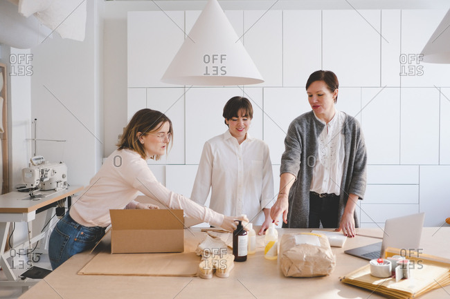 Female owners discussing over manufacturing objects at table in studio