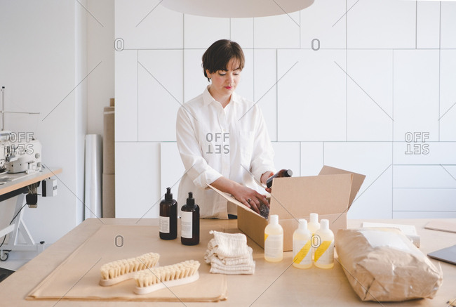 Female entrepreneur unpacking cardboard box containing bottles at table in workshop