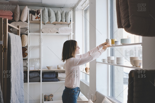 Side view of female entrepreneur arranging products on shelf in store