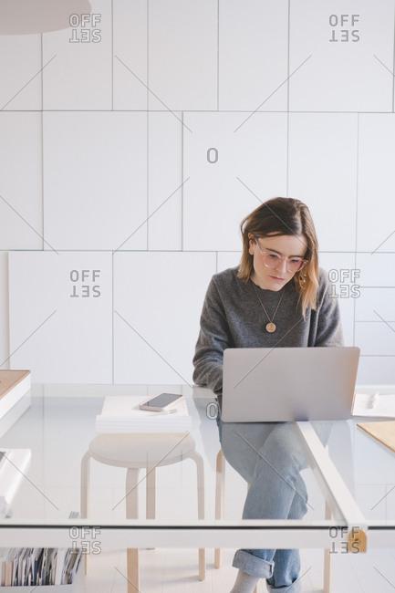 Young female entrepreneur using laptop at desk in design studio