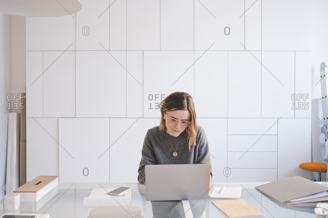 Young female entrepreneur using laptop at desk in workshop
