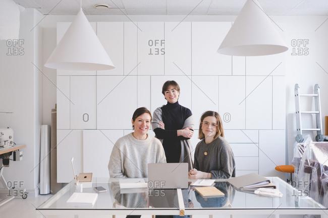 Portrait of smiling female design professionals at desk in workshop