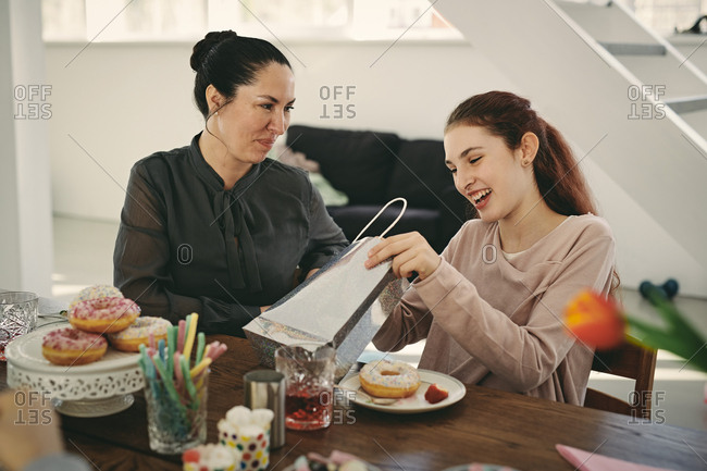 Smiling mother looking at excited daughter with gift during birthday party