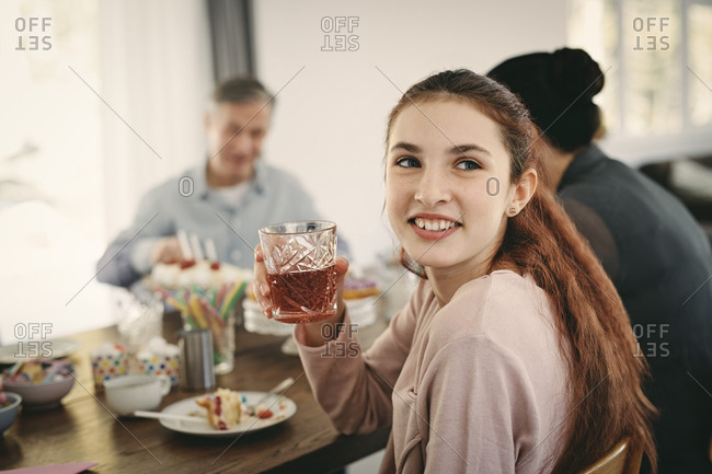 Smiling girl having drink while sitting with family at table during party
