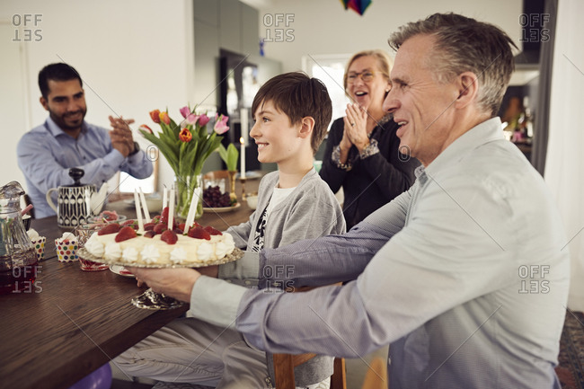Smiling family with birthday cake enjoying at party