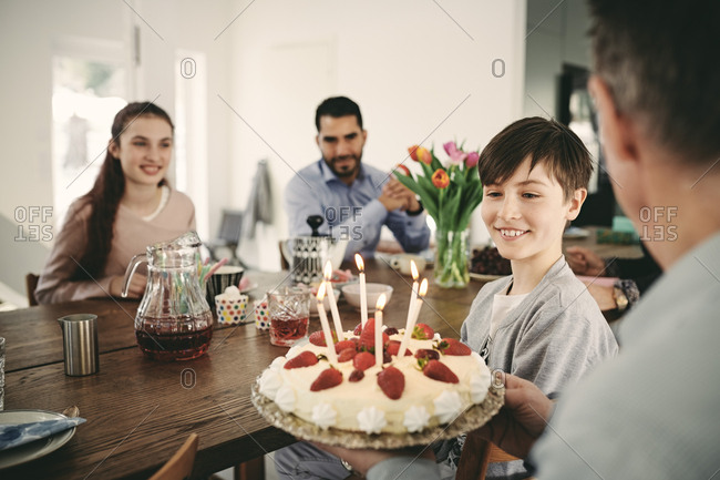 Boy looking at birthday cake while sitting with family at home