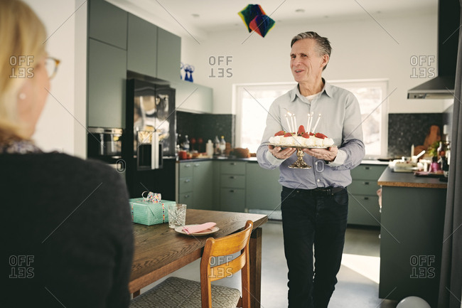 Woman looking at senior man holding birthday cake while walking by table