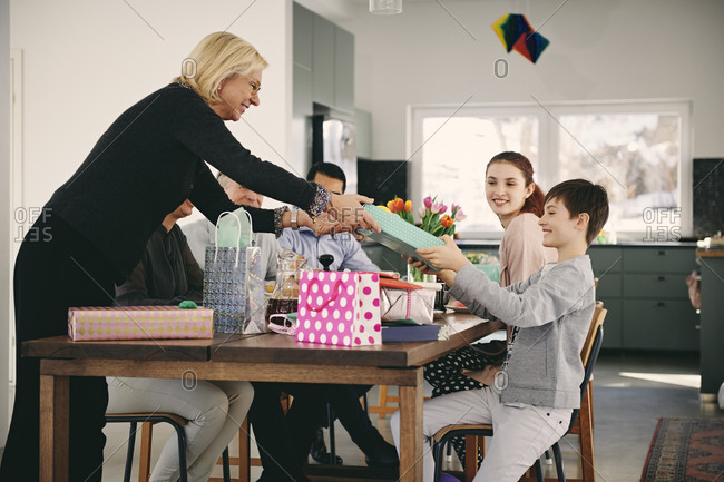 Grandmother giving gift to boy sitting with family at dining table