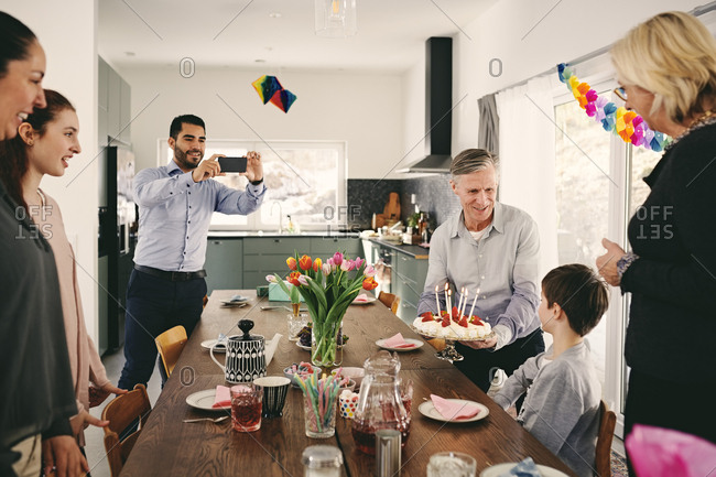 Man photographing boy with family during birthday party through smart phone