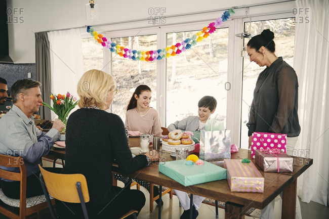 Family looking at boy with gift box while enjoying meal at table during birthday party