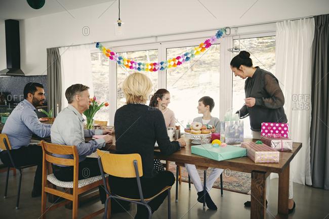 Multi-generation family enjoying food at birthday party