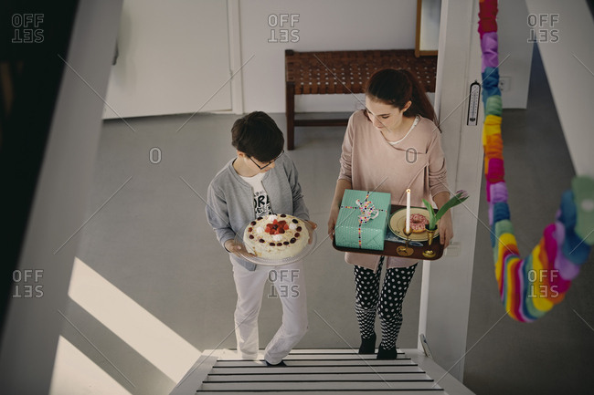 High angle view of siblings carrying birthday cake and gift box while climbing up steps at home