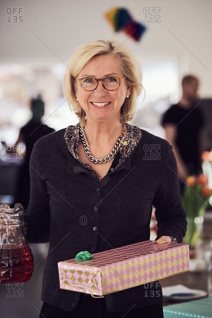 Portrait of smiling senior woman holding gift box and juice while standing at home