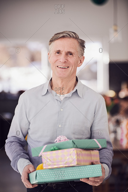 Portrait of senior man holding stacked gift boxes while standing at home
