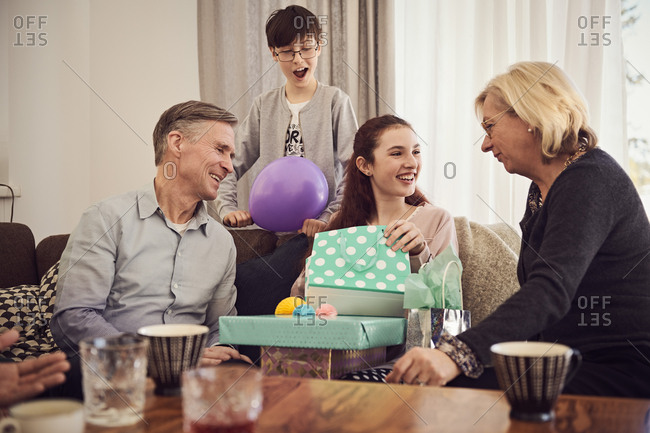 Boy looking at happy sister receiving gifts from grandparents at home