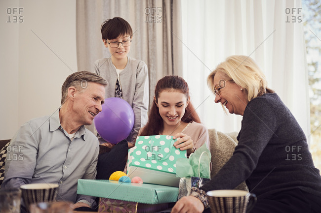 Family looking at smiling girl opening gifts on sofa at home