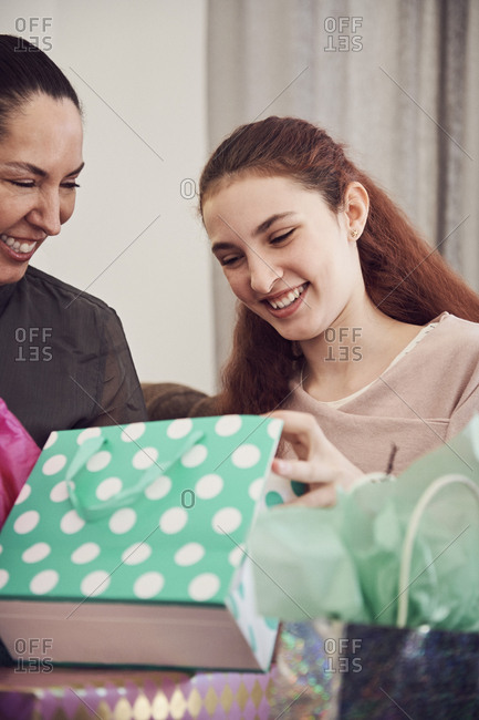 Excited girl looking at birthday present while sitting with mother at home
